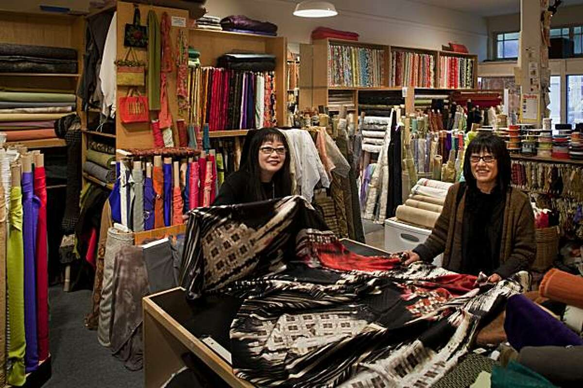 Owners Alice and Susan Miyamoto at the cutting table of their thirty-eight years old Satin Moon fabric store filled with all their hand picked fabrics in San Francisco, California on Mar. 3, 2010.