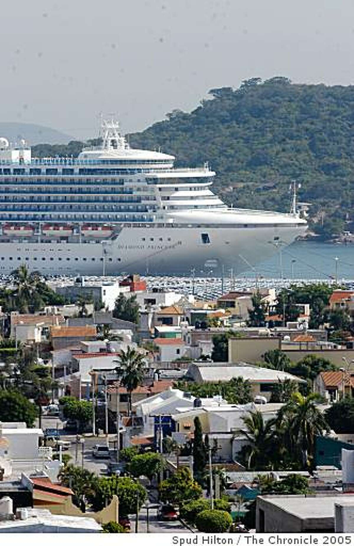 The Diamond Princess, which rises 18 stories above the water, towers over a Mazatlan neighborhood.
