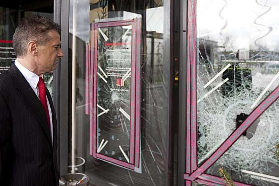 Casino managing director Michael Favrod stands in front of the smashed front door of the Grand Casino in Basel, on March 28, 2010. An armed gang of about ten masked men raided the casino packed with about 600 guests early Sunday and made off with hundredsof thousands of US  dollars, according to Swiss prosecutors. One smashed the front door with a sledgehammer, and the others ran inside with machine guns and pistols, the statement said. Photo: Patrick Straub, AP