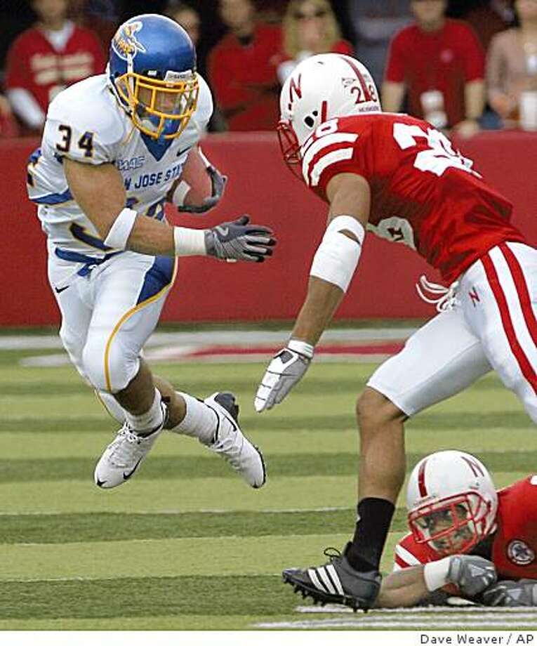 San Jose State's Yonus Davis (34) carries the ball against Nebraska's Eric Hagg, (28), with Armando Murillo, bottom right, in the first half of their NCAA college football game, in Lincoln, Neb., Saturday, Sept. 6, 2008.(AP Photo/Dave Weaver) Photo: Dave Weaver, AP