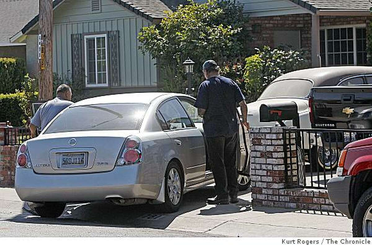 Two people enter a car in front of the home of the leader of the Mongols motorcycle club on Melanie Court in San Jose.