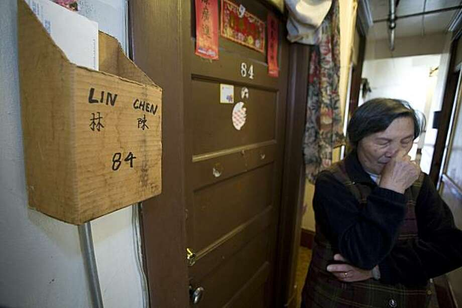 Qiao Xiu Lin a resident of the SRO (single room occupancy) hotel at 688 Commercial Street in San Francisco on Friday, March 26, 2010 has a makeshift mail box outside her apartment made out of a cardboard box. Lin said that her daughter, who lives next door is missing her paycheck from February because the Postal Service just dump mail at the desk rather than delivering it to individual rooms. Lin told her story at a press conference held by San Francisco City Attorney, Dennis Herrera and other Chinatown activists using the current Census to emphasize the point that Herrera wants the mail delivered to individuals. Kat Wade / Special to the Chronicle Photo: Kat Wade, Special To The Chronicle