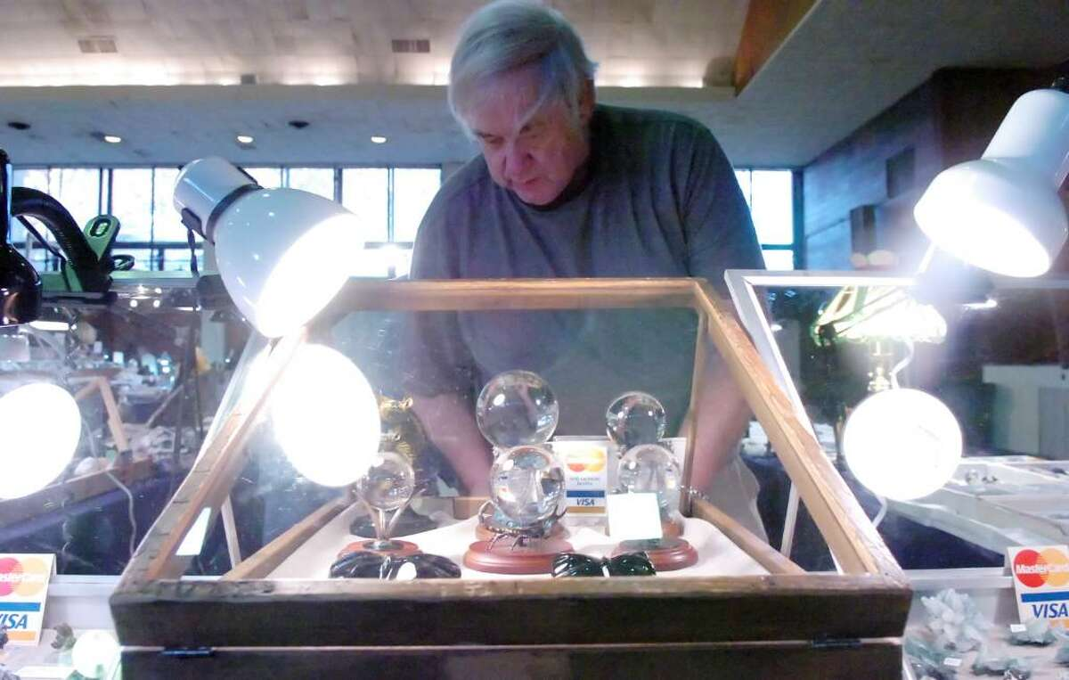 Val Collins eyes the quartz crystal balls in his Mohawk Minerals display case at the 21st Annual Gem, Mineral, Jewelry & Fossil Show at the Eastern Greenwich Civic Center Saturday afternoon, Nov. 7, 2009. The event runs through Sunday.