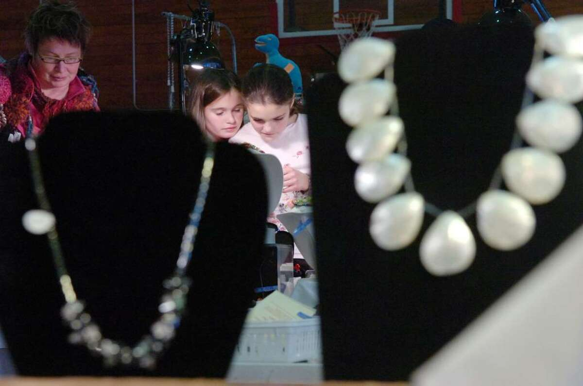 From left, Margarita Vatis, Meg Howes, 10, and Alexandra Vatis, 10, eye the jewels at the 21st Annual Gem, Mineral, Jewelry & Fossil Show at the Eastern Greenwich Civic Center Saturday afternoon, Nov. 7, 2009. The event runs through Sunday.