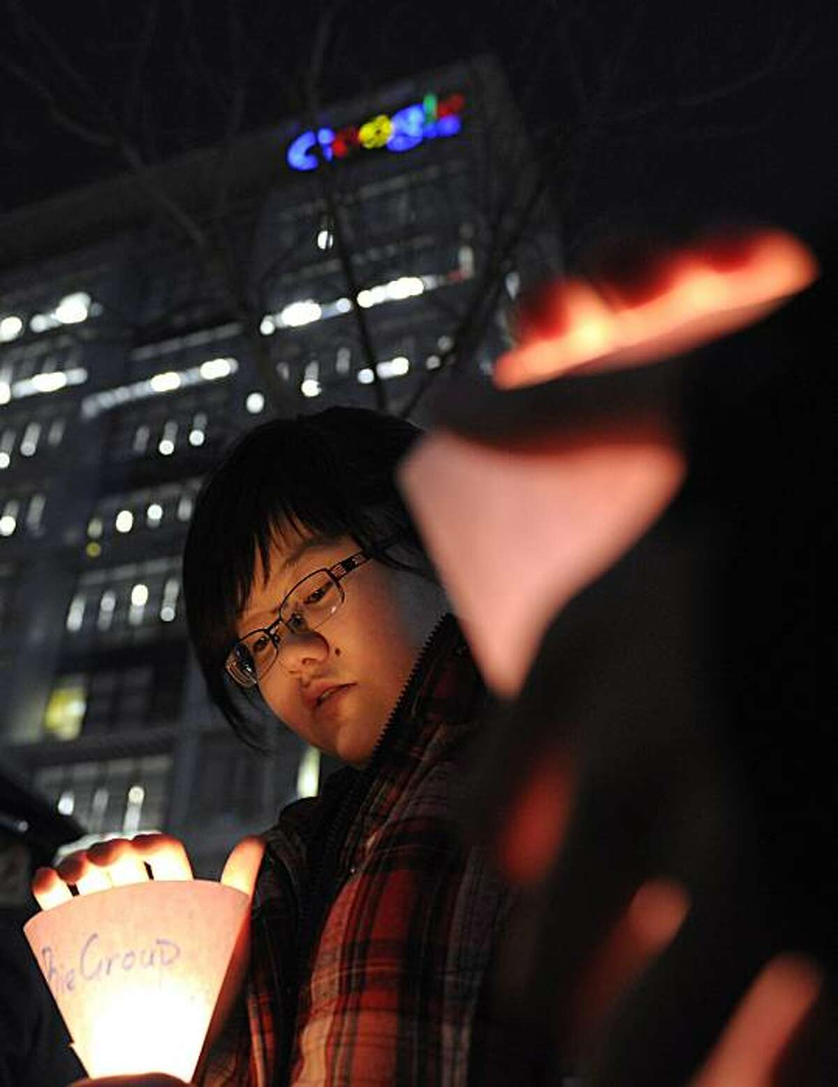 Chinese women hold candle lights in front of Google China headquarters in Beijing Tuesday, March 23, 2010. Google Inc. stopped censoring the Internet for China by shifting its search engine off the mainland Monday but said it will maintain other operations in the country. The maneuver attempts to balance Google's disdain for China's Internet rules with the company's desire to profit from an explosively growing market.