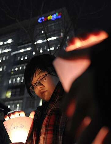 Chinese women hold candle lights in front of Google China headquarters in Beijing Tuesday, March 23, 2010. Google Inc. stopped censoring the Internet for China by shifting its search engine off the mainland Monday but said it will maintain other operations in the country. The maneuver attempts to balance Google's disdain for China's Internet rules with the company's desire to profit from an explosively growing market. Photo: Andy Wong, Associated Press