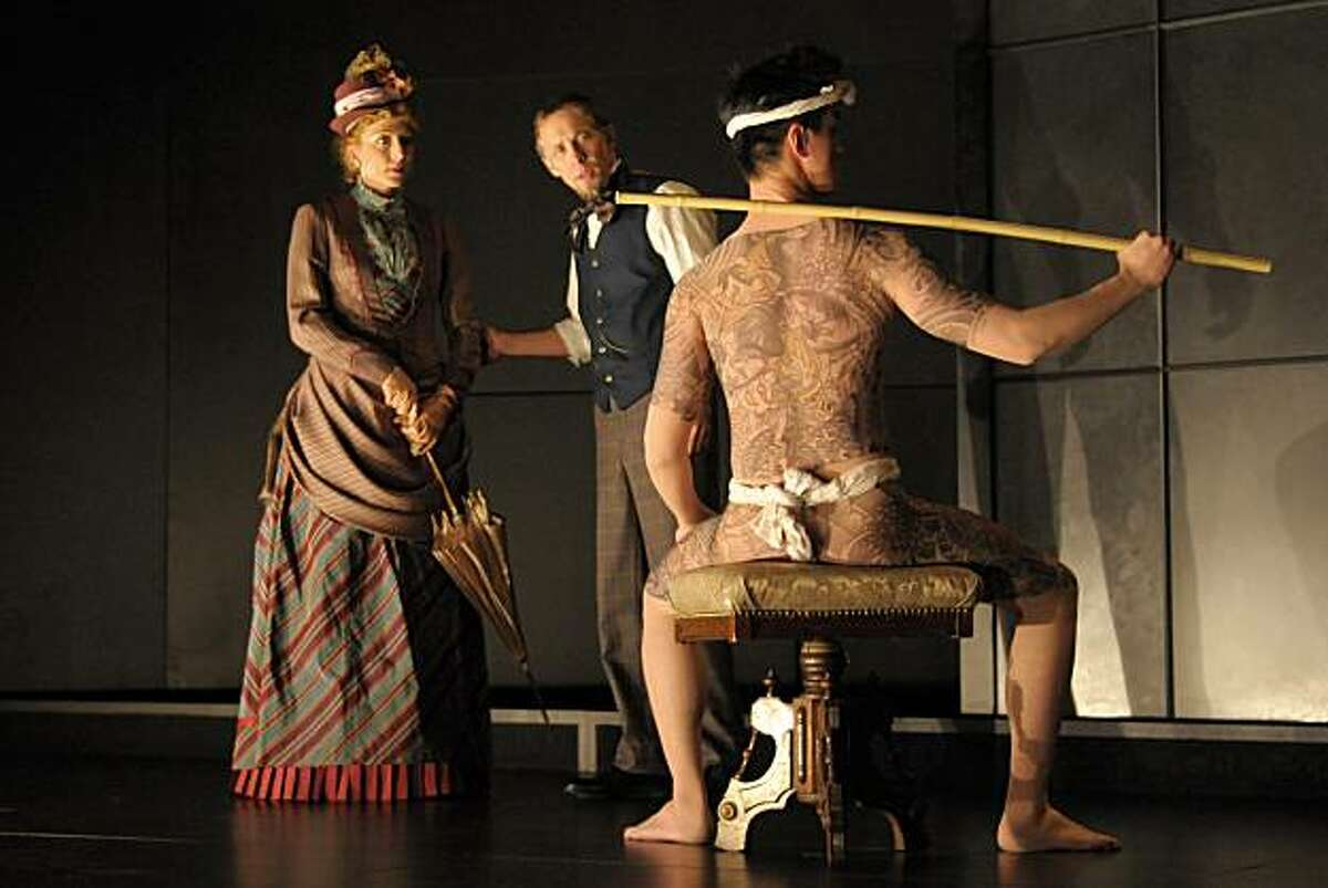 """Johnny Wu (right) models the full-body tattoos created for Berkeley Rep's world premiere of Naomi Iizuka's """"Concerning Strange Devices from the Distant West"""" as Kate Eastwood Norris and Bruce McKenzie look on."""