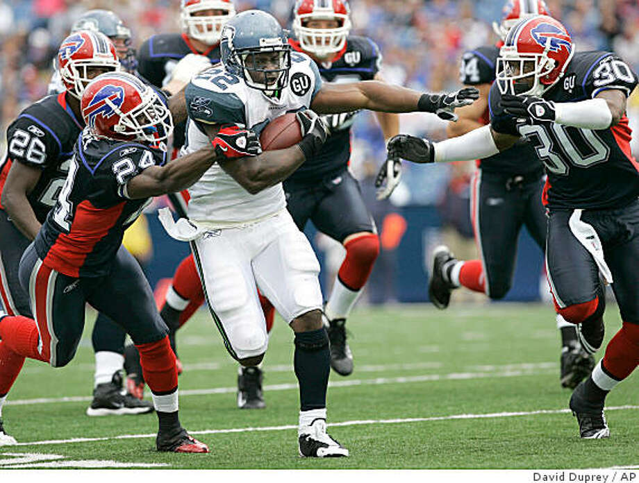 Seattle Seahawks' Julius Jones (22) runs under pressure from Buffalo Bills' Terrence McGee (24) and Ko Simpson (30) during the second half of an NFL  football game at Ralph Wilson Stadium in Orchard Park, N.Y., Sunday, Sept. 7, 2008. The Bills won 34-10. (AP Photo/David Duprey) Photo: David Duprey, AP