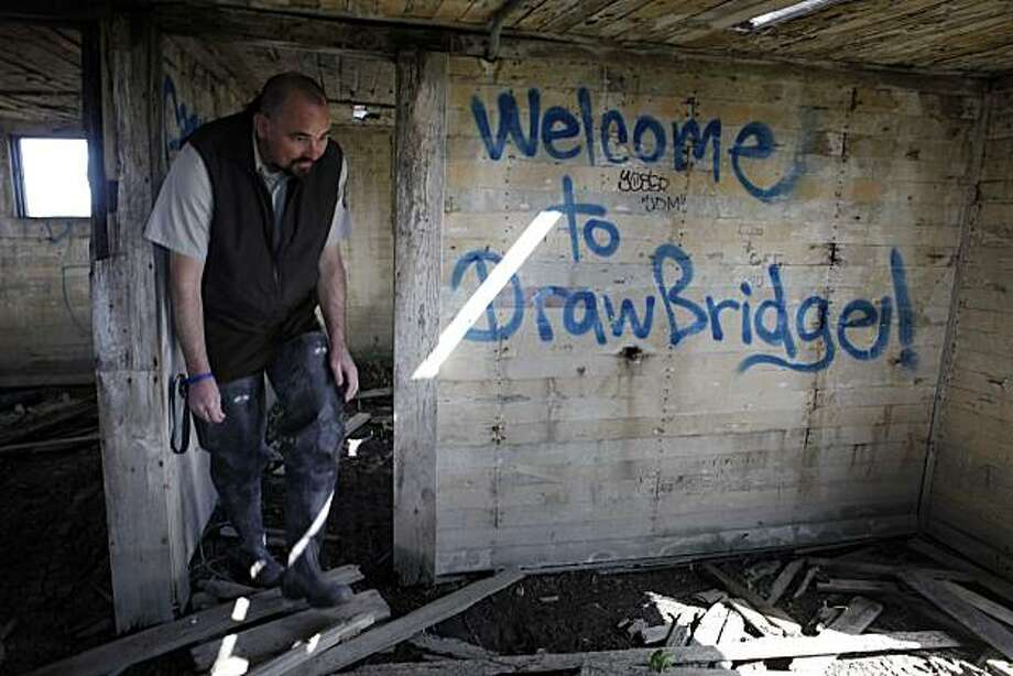 Eric Mruz, manager of the Don Edwards San Francisco Bay National Wildlife Refuge investigates a dilapidated building in historic Drawbridge, an abandoned fishing and hunting community located on the Don Edwards San Francisco Bay National Wildlife Refuge near San Jose, are being naturally reclaimed by the south bay salt flats on Tuesday March 23, 2010 in Drawbridge, Calif. Photo: Mike Kepka, The Chronicle