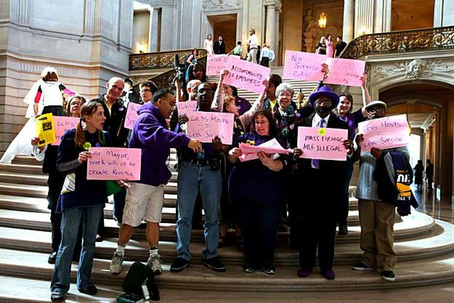 Members of the the SEIU gather by City Hall's rotunda for a portrait after protesting against Mayor Newsom's decision to send pink slips to over 17,000 workers in public health, libraries, parks, MUNI and other vital services on Friday, Mar. 19, 2010 in San Francisco, Calif. Photo: Jessica Pons, The Chronicle