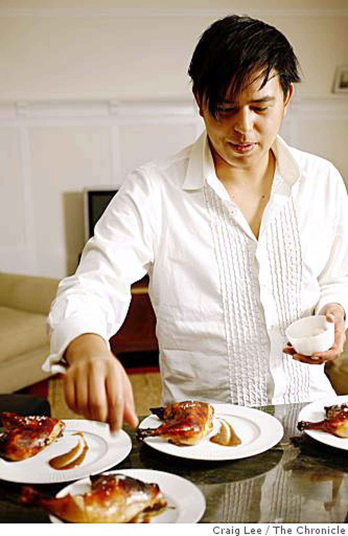 Drey Roxas, chef at Palencia restaurant, preparing a Filipino dish, Lechon na manok sa hurno (baked chicken) at his home in San Francisco, Calif., on August 11, 2008. He is placing salt on the finished dish.