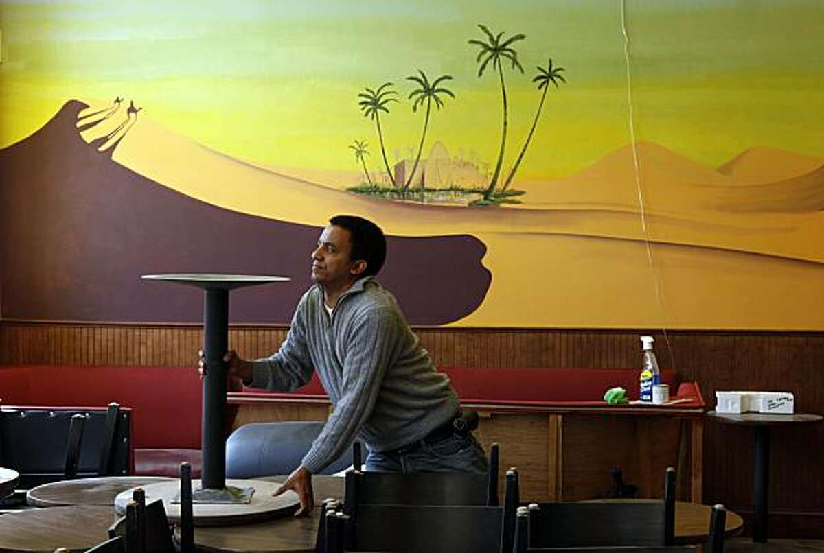 Cafe Oasis owner Taddesse Haile, moves furniture in his new coffee house, which is scheduled to open at the end of the month at 901 Divisadero.