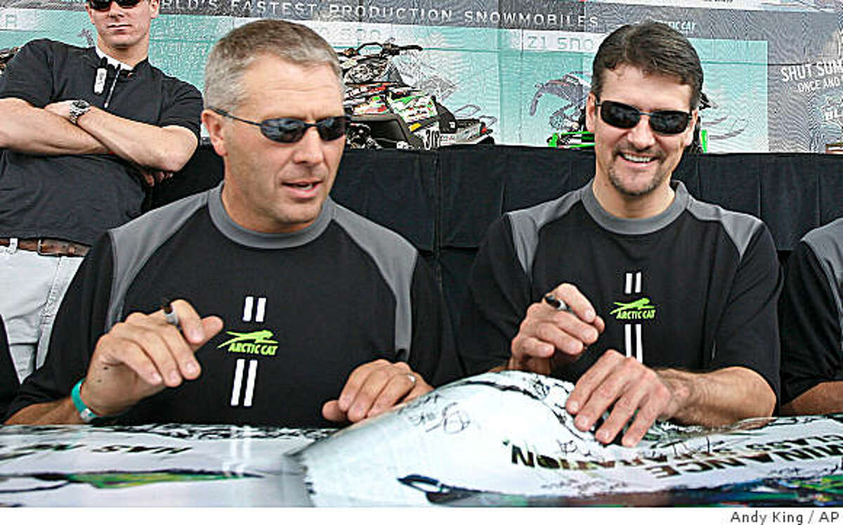 Todd Palin (right), husband of former Republican vice presidential candidate, Sarah Palin, signs autographs with professional snowmobile partner Scott Davis at the Hays Days Grass Drags snowmobile event in Forest Lake, Minn. Palin was the defending and four-time champion of the 1,971-mile Iron Dog snowmobile race while Davis is a seven-time champion in his home state of Alaska. (2008 file photo.)