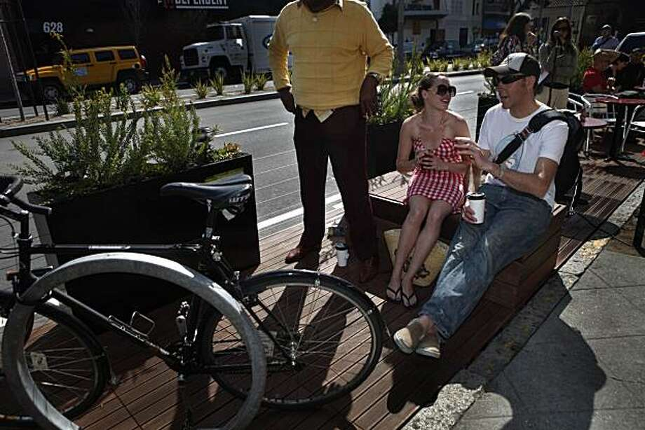 Meaghan Johnson (second from right) and Rad Hall (right) both talk in the new parklet on Divisadero street between Hayes and Grove Streets in San Francisco, Calif. on Thursday, March 18, 2010.  Johnson said it was her fourth time in a week she had been to the parklet. It was Hall's first time. Photo: Lea Suzuki, The Chronicle