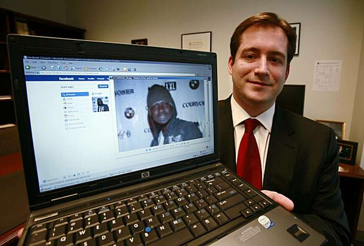 FILE - In this Oct. 13, 2009, file photo, Assistant U.S. Attorney Michael Scoville displays part of the Facebook page, and an enlarged profile photo, of fugitive Maxi Sopo in Seattle. The Feds are on Facebook. And MySpace, LinkedIn and Twitter, too. U.S.law enforcement agents are following the rest of the Internet world into popular social-networking services, going undercover with false online profiles to communicate with suspects and gather private information, according to an internal Justice Department document that offers a tantalizing glimpse of issues related to privacy and crime fighting.