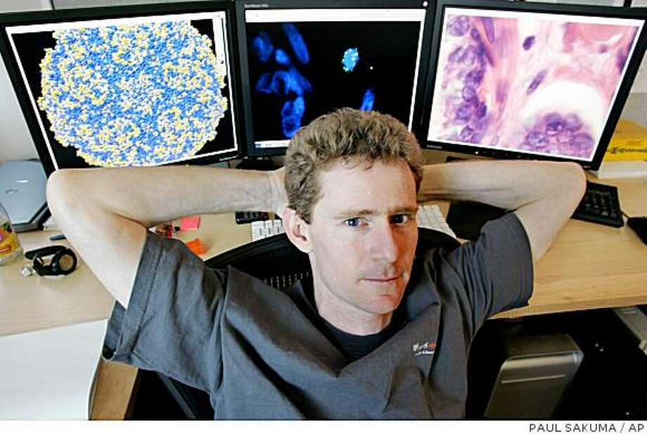 University of California, San Francisco researcher Joe DeRisi poses with photos on his computer of a virus structure, left, prostate tissue, center, and another virus, right, in his office in San Francisco, Wednesday, Feb. 22, 2006. On Friday, Feb. 24, 2006, researchers at the UCSF and the Cleveland Clinic plan to announce they had found a virus never before seen in humans in cancerous prostates removed from men with a certain genetic defect. (AP Photo/Paul Sakuma)Ran on: 02-25-2006 Joseph DeRisi, a UCSF medical researcher, sits by photos of (from left) a virus structure, prostate tissue and another virus.Ran on: 02-25-2006 Photo: PAUL SAKUMA, AP
