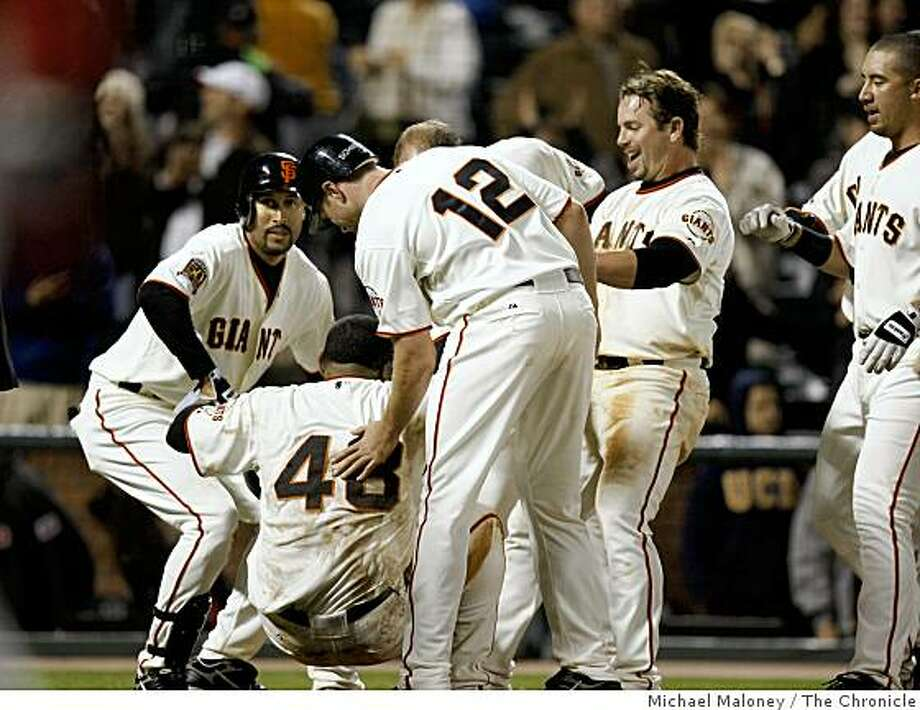 San Francisco Giants Pablo Sandoval (48) is helped up by his team after scoring in the bottom of the ninth. Photo: Michael Maloney, The Chronicle