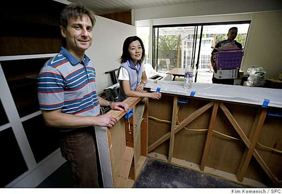 Dario, left and Tomoko Boffelli stand in their yet-to-be-completed kitchen as movers help them move in to their new home in San Mateo, Calif. Photo: Kim Komenich, SFC
