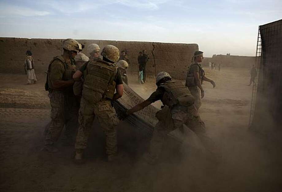 TO GO WITH HEIDI VOGT STORY SLUGGED:  BC-AS--Afghanistan-Fear Campaign-- In this image taken Monday, March 15, 2010, in Marjah, marines of the First Battalion, Sixth Marine Regiment build a barrier around their base. Taliban insurgents are conducting a fear and intimidation campaign against residents of the southern Afghan town of Marjah, which international forces just wrested from insurgents. Photo: Dusan Vranic, AP