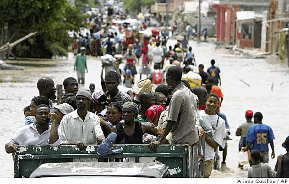 Flood victims leave the area in the back of a truck through flooded streets after Tropical Storm Hanna hit the area in Gonaives, Saturday, Sept. 6, 2008.  Hanna has killed 166 people in Haiti. (AP Photo/Ariana Cubillos) Photo: Ariana Cubillos, AP