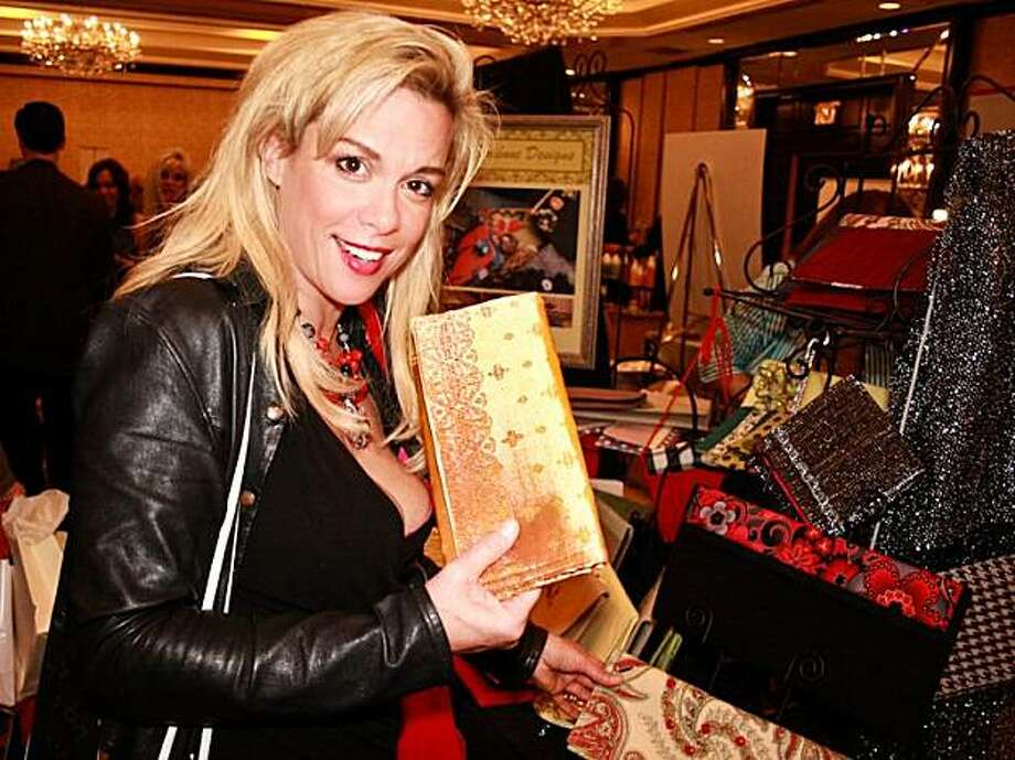 """Star Trek"" star Chase Masterson picks up a bag made by Chelsea Schick at the Academy Awards Style Lounge on March 6 in Hollywood. Photo: Leah Banks"