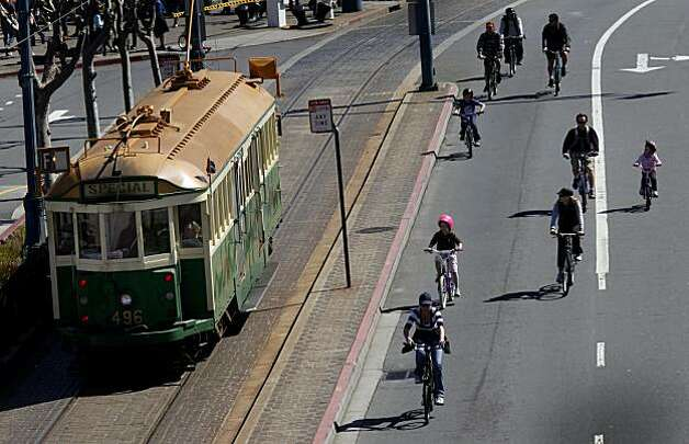 Bicyclists race a streetcar down the Embarcadero near Pier 39 during San Francisco's first Sunday Streets event of the year, which shut down the Embarcadero from the AT&T Park to Pier 45. Photo: Brant Ward, The Chronicle