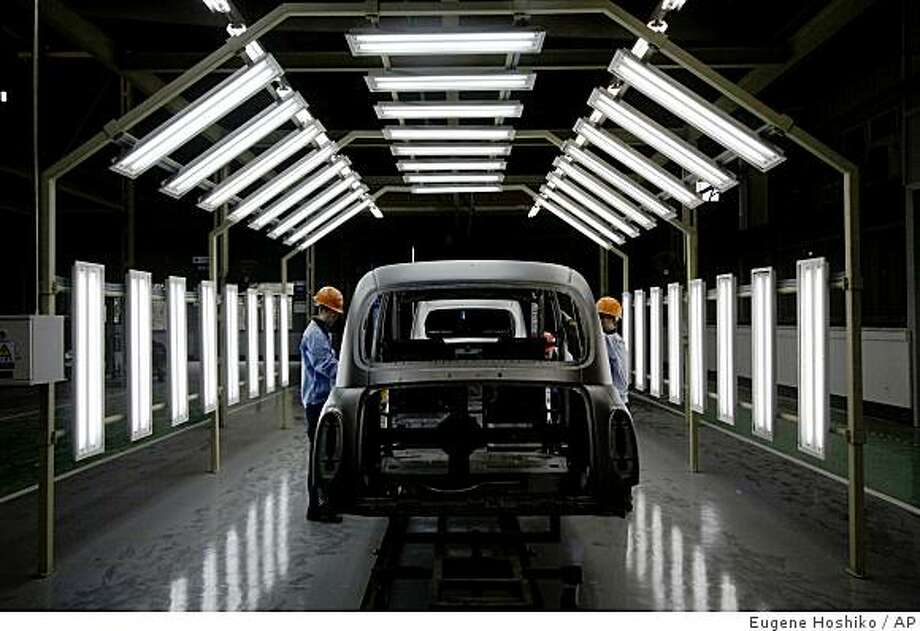 Workers check the chassis of the London Taxi's TX4 as trial operation at their new factory Friday Aug. 29. 2008 in Fengjing, China. London Taxis are as British as bowler hats and Big Ben. But the latest models coming off this new assembly line are unlikely to ever touch an English road.  (AP Photo/Eugene Hoshiko) Photo: Eugene Hoshiko, AP