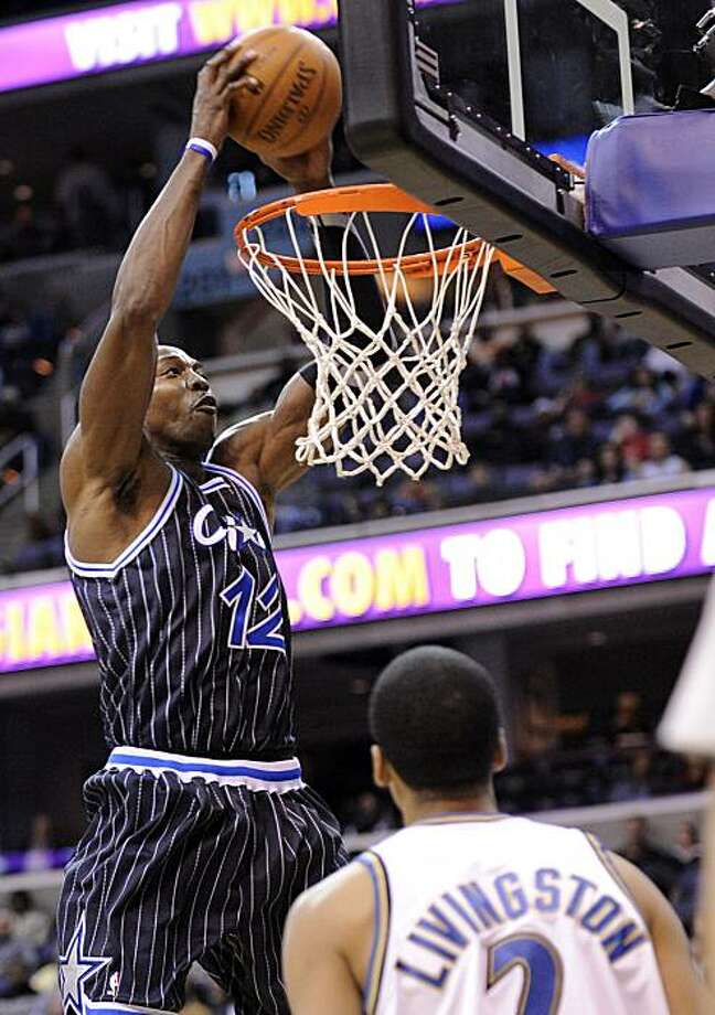Orlando Magic center Dwight Howard (12) goes to the basket against Washington Wizards guard Shaun Livingston (2) during the first half of an NBA basketball game, Saturday, March 13, 2010, in Washington. Photo: Nick Wass, AP