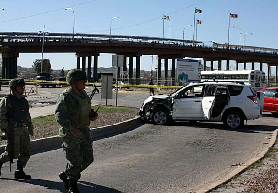 Soldiers patrol a crime scene where a crashed car sits in Ciudad Juarez, Sunday, March 14, 2010.  A U.S. consulate employee and her husband were shot to death Saturday in their car near the Santa Fe International bridge linking Ciudad Juarez with El Paso,Texas, and their baby was found unharmed in the back seat, according to Vladimir Tuexi, a spokesman for Chihuahua state prosecutors' office. Photo: AP