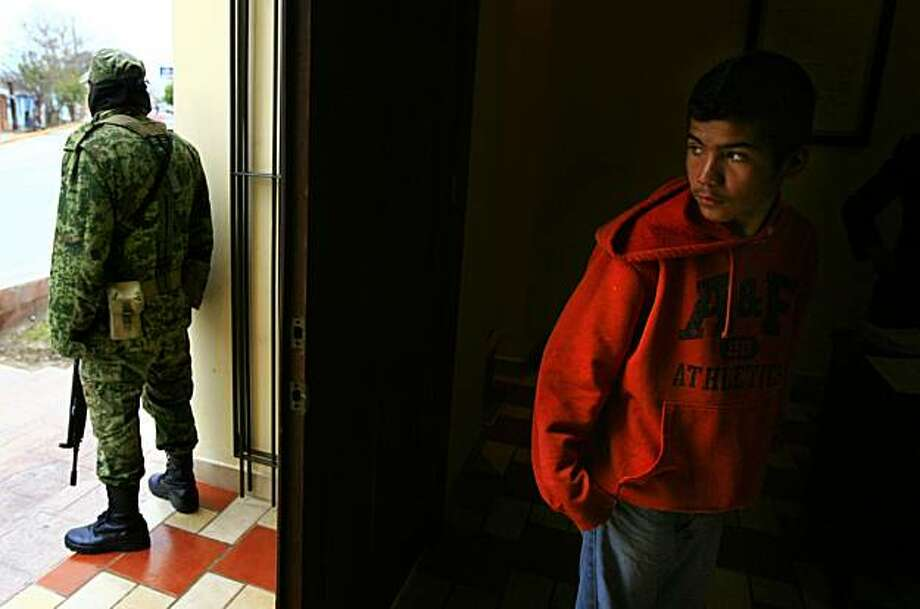 In this photo taken on  March 5, 2010, Juan Manuel Parra, 13, right, looks out the door of the Reynosa Municipal Archives building as a member of the Mexican Army stands guard in Reynosa, Mexico. The army held a exhibit for the public to learn about military personnel and their presence in the border city. Parra's mother said her son is considering joining the military when he is old enough.  (AP Photo/The Monitor, Nathan Lambrecht) TV OUT, INTERNET OUT, MAGS OUT, NO SALES Photo: Nathan Lambrecht, AP