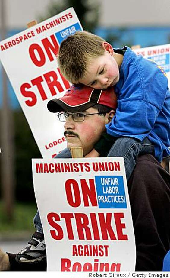 EVERETT, WA - SEPTEMBER 06:  Boeing machinist Scott Green, with his son Joshua, 3,on his shoulders, walks the picket line outside Boeing's plant September 6, 2008 in Everett, Washington. Around 27,000 machinists are striking from the states of Washington State, Oregon and Kansas as Boeing faces its second major strike in three years.  (Photo by Robert Giroux/Getty Images) Photo: Getty Images