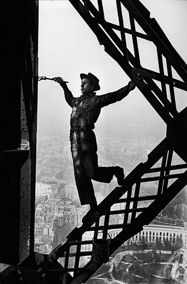 (EIFFEL TOWER) MAN  PAINTING THE EIFFEL TOWER WITHOUT A SAFETY BELT MORE THAN 900 FEET ABOVE PARIS, PARIS, 1953 Photo: Marc Riboud