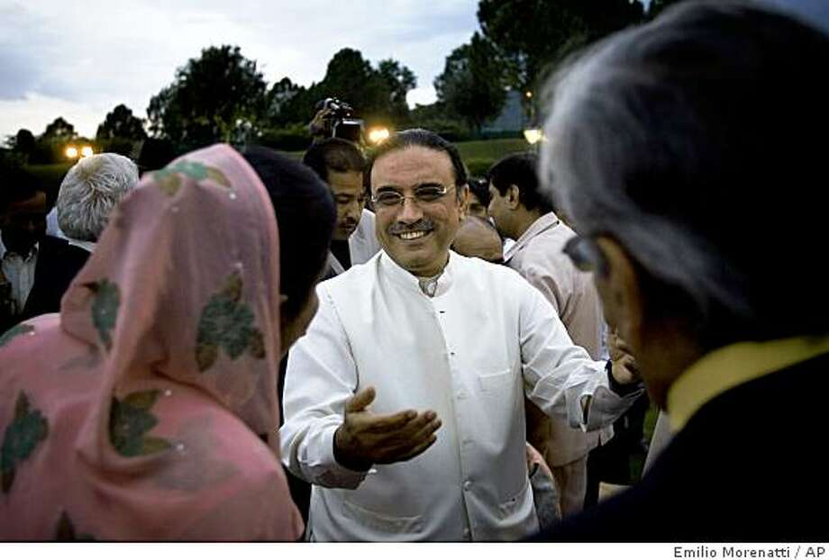 Pakistani President elect Asif Ali Zardari, center, head of the ruling Pakistan People's Party and widower of two-time Prime Minister Benazir Bhutto, is congratulated by party members during a celebration dinner at the Prime Minister residence in Islamabad, Pakistan on Saturday, Sept. 6, 2008. The widower of slain former premier Benazir Bhutto became Pakistan's new president Saturday after winning a landslide election victory that makes him a critical partner of the West against international terrorism. (AP Photo/Emilio Morenatti) Photo: Emilio Morenatti, AP