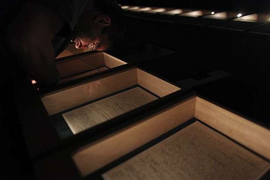 An Israeli curator checks the light in a case holding one of the papers from the manuscript of Albert Einstein's general theory of relativity at the Academy of Sciences and Humanities in Jerusalem, Sunday, March 7, 2010. The original manuscript of AlbertEinstein's groundbreaking theory of relativity, which underlies everything from black holes to the Big Bang, goes on display in its entirety Sunday for the first time. Photo: Tara Todras-Whitehill, AP
