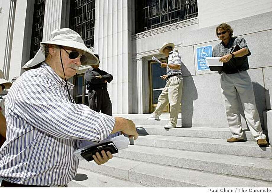 Real estate investment specialist Robert Kramer, left, listens to auctioneer Marc Ramsland, right, name a long list of foreclosed properties scheduled for sale at auction on the steps of the Alameda County Courthouse in Oakland, Calif., on Wednesday, Sept. 3, 2008. Photo: Paul Chinn, The Chronicle
