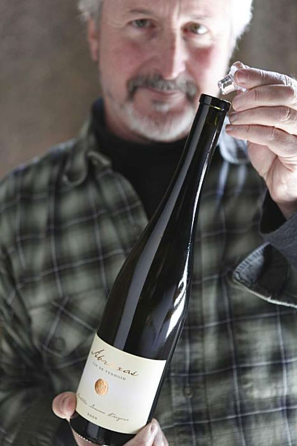 Robert Sinskey, owner and vintner at Robert Sinskey Vineyards demonstrates the simplicity used to opening a Vino-Lok closure, made from glass, instead of a traditional cork on Tuesday March 9, 2010 in Napa, Calif.