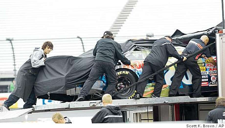 Crewmembers secure the Nationwide race car of Joey Legano inside the hauler as inclement weather from Tropical Storm Hanna approaches at Richmond International Raceway Friday Sept. 5, 2008 in Richmond Va. NASCAR postponed all weekend activities including the Nationwide series race and the Sprint Cup series race till Sunday.(AP Photo/Scott K. Brown) Photo: Scott K. Brown, AP