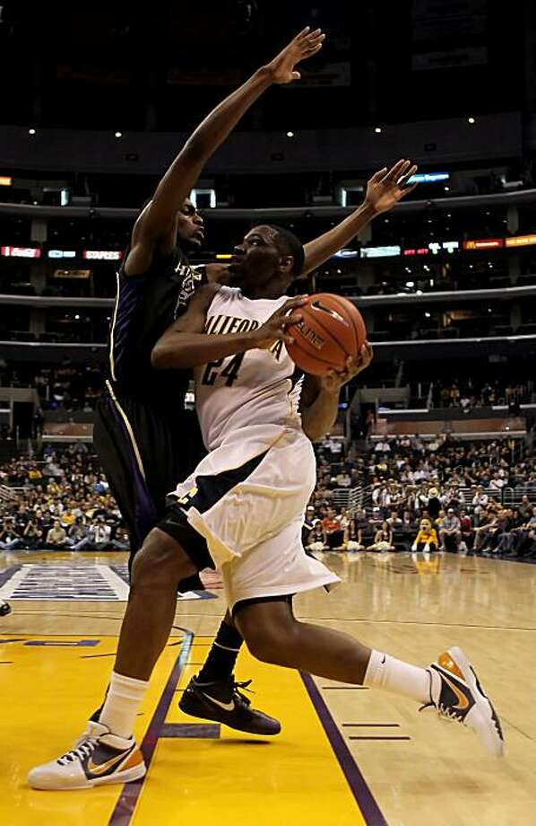 Theo Robinson of the Cal Golden Bears drives to the basket while being defended by Justin Holiday of the Washington Huskies in the first half during the championship game of the Pac-10 Basketball Tournament at StaplesCenter on Saturday in Los Angeles. Photo: Jeff Gross, Getty Images