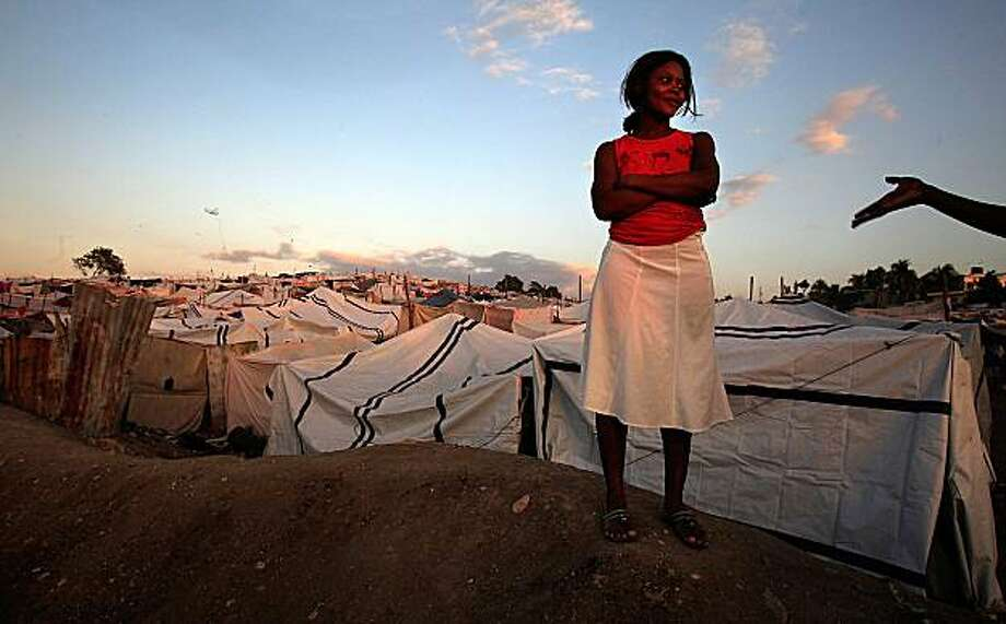 A young Haitian man, at right, flirts with a young Hatian woman as life goes on inside the Daihatsu tent camp on the outskirts of Port au Prince, Haiti, January 25, 2010. (Brian Vander Brug/Los Angeles Times/MCT) Photo: Brian Vander Brug, MCT