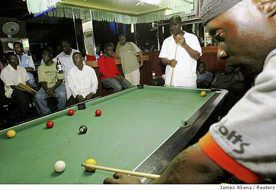 Ugandans play a game of pool during during a weekly cocktail night at Club Volts in the capital Kampala in this August 25, 2007 file photo. This photo accompanies the TRAVEL-KAMPALA/ piece by Reuters journalist Daniel Wallis, who uses his local knowledge to help visitors get the most from a short stay in the Ugandan capital. To match Life TRAVEL-KAMPALA/ REUTERS/James Akena/Files (UGANDA) Photo: James Akena, Reuters