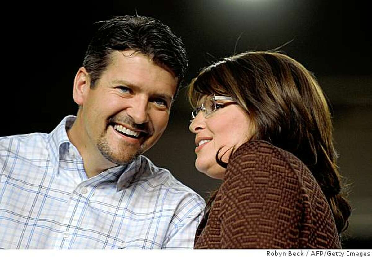 Republican vice presidential candidate Sarah Palin talks with her husband Todd Palin during a campaign event at the Albuquerque Convention Center in Albuquerque, New Mexico on September 6, 2008. AFP PHOTO Robyn BECK (Photo credit should read ROBYN BECK/AFP/Getty Images)