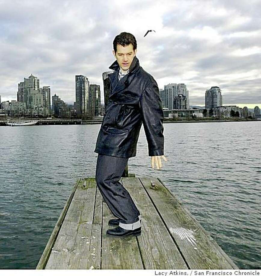 "Chris Isaak, stands on the dock, ""This is the closes thing I get to surfing here"", Isaak jokes as he pretends he's on a surfboard on the bay in Vancouver, Wed. Feb.7, 01. Photo: Lacy Atkins,, San Francisco Chronicle"
