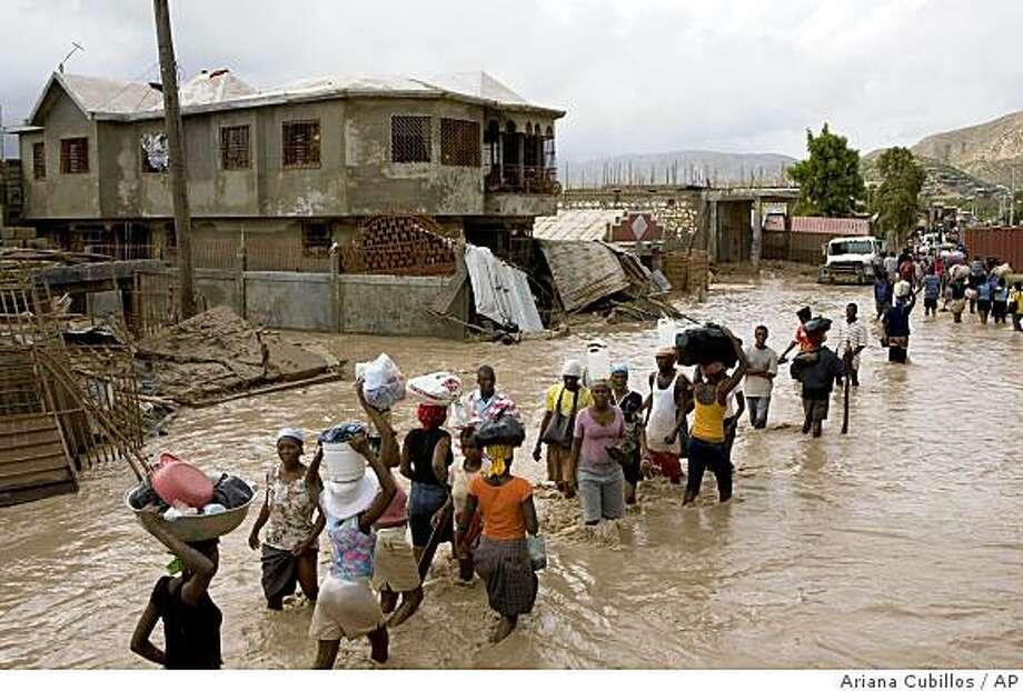 People wade through flooded streets after Tropical Storm Hanna hit the area in Gonaives, Haiti, Wednesday, Sept. 3, 2008.  Three storms have killed at least 126 people in Haiti in less than three weeks and even as Tropical Storm Hanna edged away, forecasters warned that a fourth storm Hurricane Ike could hit the Western hemisphere's poorest country as a major storm next week. (AP Photo/Ariana Cubillos) Photo: Ariana Cubillos, AP