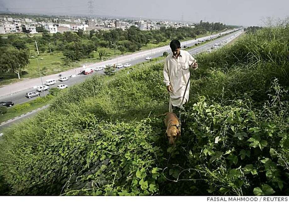Pakistani security personnel along with sniffer dogs secure an area, after an attack on the motorcade of Prime Minister Yousaf Raza Gilani, near the airport in Islamabad September 3, 2008. Shots were fired at Gilani's motorcade near Islamabad's airport on Wednesday but officials and police said he was not in it at the time. REUTERS/Faisal Mahmood (PAKISTAN) Photo: FAISAL MAHMOOD, REUTERS