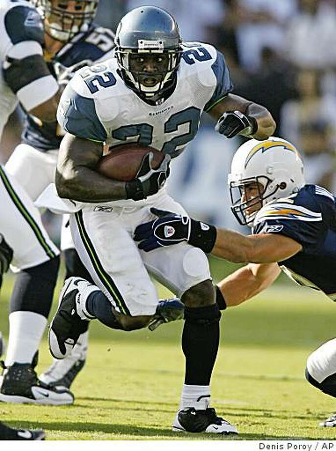 Seattle Seahawks running back Julius Jones (22) breaks away from the tackle of San Diego Chargers' Matt Wilhelm, right, during the first quarter of an NFL preseason football game Monday, Aug. 25, 2008, in San Diego. (AP Photo/Denis Poroy) Photo: Denis Poroy, AP