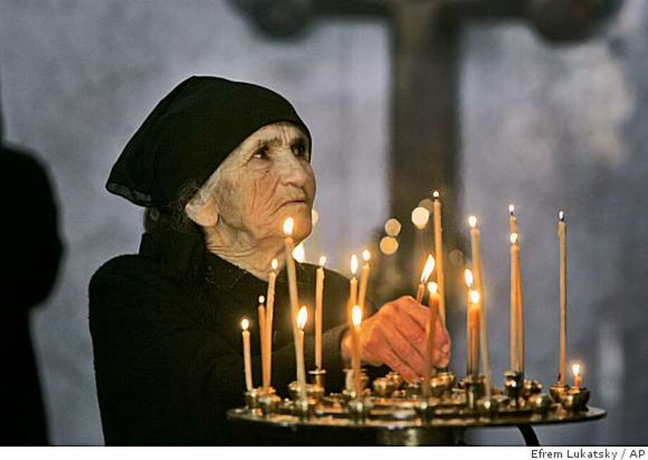 """A Georgian woman lights candles in an Orthodox Cathedral in Tbilisi Georgia, Wednesday, Sept. 3, 2008.  The Georgian parliament at its plenary meeting on Wednesday will discuss the issue """"on lifting the martial law in the country."""" Parliament speaker David Bakradze said that """"there is no need any longer to have a martial law in the country."""" However, he noted, """"a state of emergency will be introduced in those Georgian regions where illegally brought in the country Russian armed forces are deployed.""""(AP Photo/Efrem Lukatsky) Photo: Efrem Lukatsky, AP"""