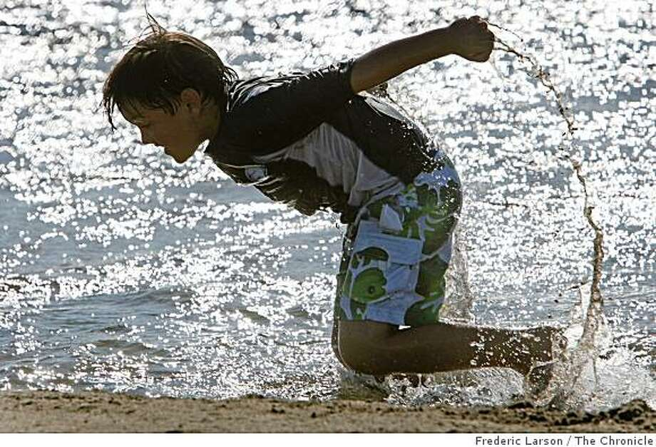 Michael Silva (9) of San Francisco who is silhouetted by the sun frolics in a shallow pool of water at Crissy Beach in San Francisco, Calif., on September 2, 2008. Photo: Frederic Larson, The Chronicle