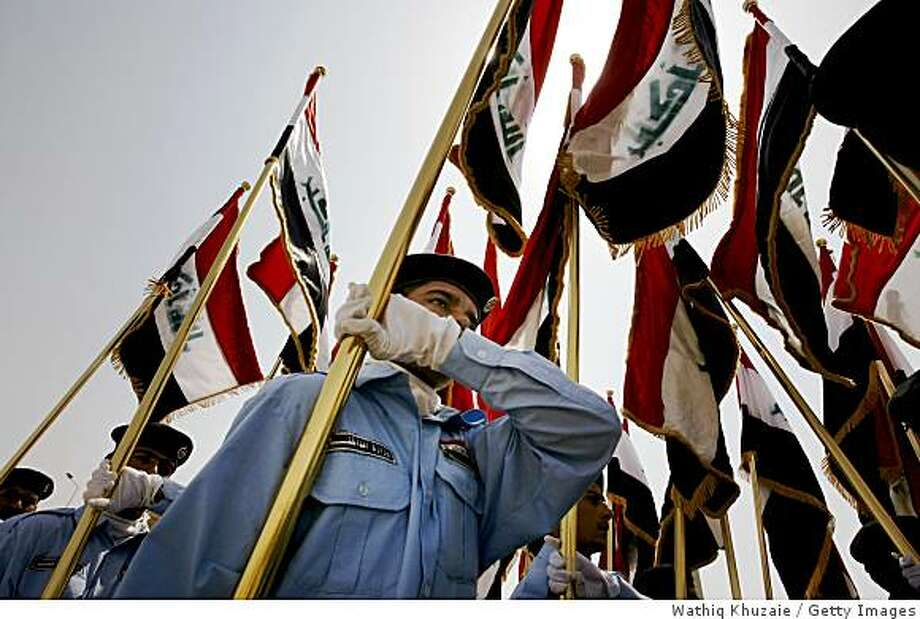RAMADI, IRAQ - SEPTEMBER 1: Iraqi security forces carry Iraqi flags during a handover ceremony at the government headquarters September 1, 2008 in Ramadi, the capital of Anbar province, 180 km west of Baghdad, Iraq. The U.S. military handed over the security control of Iraq's biggest province Anbar, once the centre of Iraq's Sunni insurgency, to the Iraqi security forces in a ceremony held at the government headquarters in the provincial capital of Ramadi. (Photo by Wathiq Khuzaie /Getty Images) Photo: Wathiq Khuzaie, Getty Images