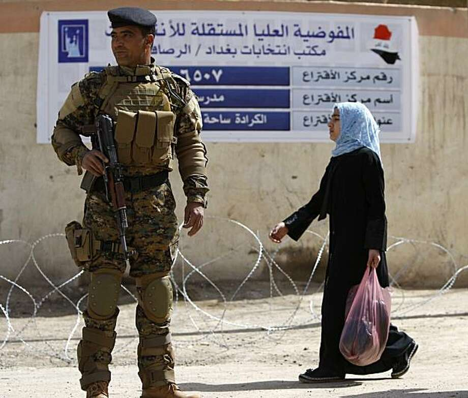 An Iraqi girl walks past a soldier securing the entrance to a polling centre in central Baghdad on March 6, 2010 a day before the country's general election. Al-Qaeda in Iraq has threatened to kill people who vote in the war-torn nation's election on March 7 and imposed a self-declared curfew during polling hours when millions will cast ballots. Photo: Ahmad Al-rubaye, AFP/Getty Images