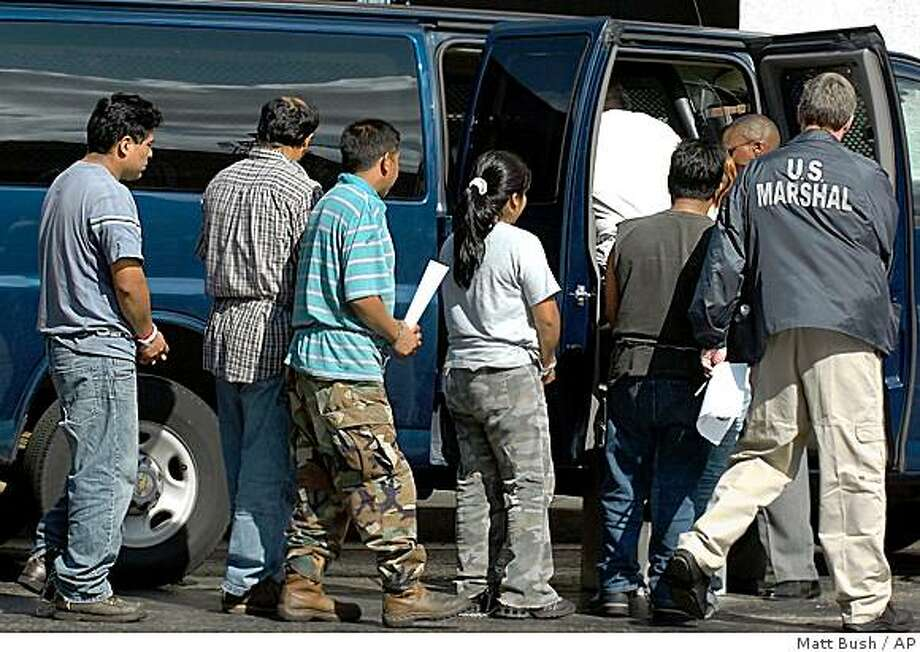 Detainees netted in a Department of Homeland Security Immigration and Custom Enforcement raid at Howard Industries manufacturing plant in Laurel, Miss. are escorted out of the Federal court house in Hattiesburg, Miss., Tuesday, Aug. 26, 2008. Federal officials say nearly 600 suspected illegal immigrants were detained in a raid on a manufacturing plant in southern Mississippi, making it the largest such sweep in the country. (AP Photo/Matt Bush, The Hattiesburg American) Photo: Matt Bush, AP
